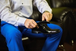 Groom wearing shoes on wedding day, man's style, man legs and hands tying shoe laces, business man dressing up with classic, elegant shoes