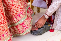 Groom wearing the ring on bride's toe finger, traditional indian hindu wedding ritual during marriage ceremony