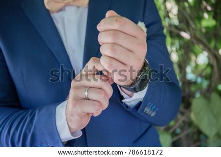 groom wears a watch #786618172