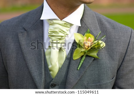 groom with orchid buttonhole and green cravat at a wedding