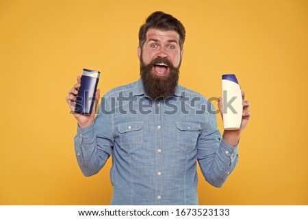 Grooming at every opportunity. Bearded man hold shampoo bottles yellow background. Cosmetics and toiletries. Hygiene and personal grooming. Male body grooming and skincare. Grooming products for men.