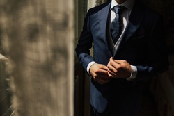 Grooms morning preparation. Cropped photo of elegant young fashion man dressing up for wedding celebration. Groom dressed in modern blue formal suit, white shirt getting ready for event. Sunny morning