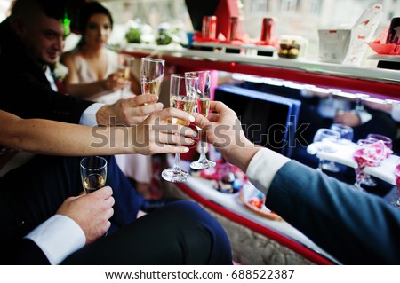 Groomsmen and bridesmaids drinking champagne in the limo.