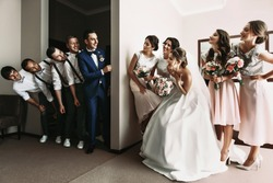 Groomsmen & Bridesmaids having fun & posing in hotel room