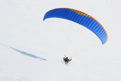 Gros plan paramotor flying in winter in a snow-white landscape seen from the ciel