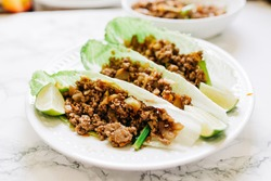 Ground Beef Lettuce Wraps on a plate with lime edges. These lettuce wraps are using romaine lettuce.