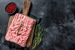Ground chicken or turkey raw meat on wooden board. Black background. Top View. Copy space