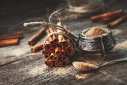 Ground cinnamon, cinnamon sticks, tied with jute rope on old wooden background in rustic style