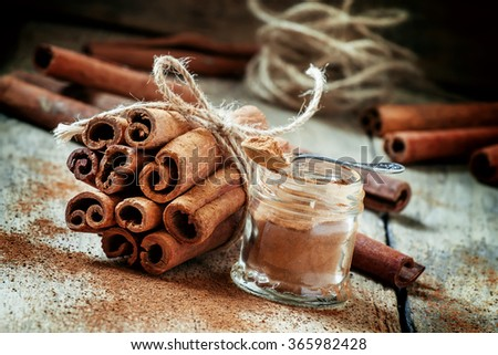 Ground cinnamon, cinnamon sticks, tied with jute rope on old wooden background in rustic style, selective focus