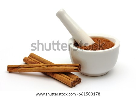 Ground cinnamon in a bowl with cinnamon sticks isolated on white background