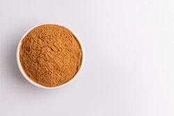 Ground cinnamon isolated in a white bowl, on white background, copy space, studio shot, soft light,  top view.  Latin name  Cinnamomum cassia