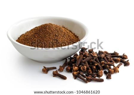 Ground cloves in white ceramic bowl isolated on white. Whole cloves.