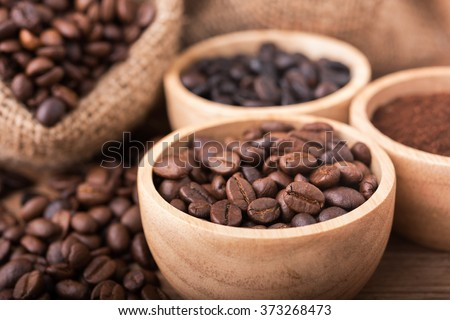 Ground coffee and coffee beans in the wood bowls, background is the coffee bags on the wooden table