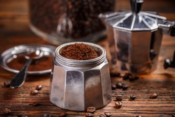Ground coffee and moka pot coffee maker over rustic wooden background