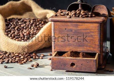 Ground coffee in vintage grider and beans in sack