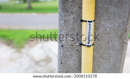 Ground conduit on pole-closeup. The master ground conduit of the short circuit protection system installed on the side of the concrete power pole with copy space. Selective focus Stock photo ©