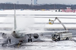 Ground crew provides de icing. They are spraying the aircraft, which prevents the occurrence of frost