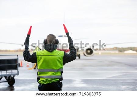 Ground Crew Signaling To Airplane #719803975
