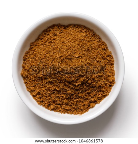 Ground cumin in white ceramic bowl isolated on white from above.