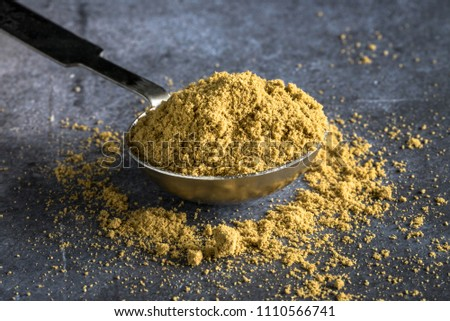 Ground Cumin Spilled from a Teaspoon