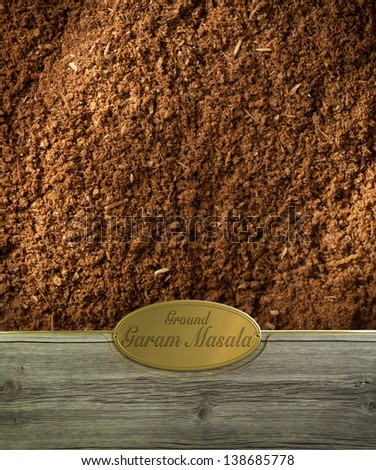 Ground Garam masala spices frame in wood with a golden label