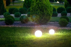 ground garden lantern with light glare by electric lamp with a ball diffuser in the green grass on background evergreen thuja bushes in a landscaped park night scene, nobody.