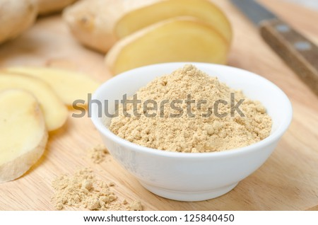 ground ginger in white bowl on a wooden board