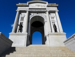 Ground-level shot of a large monument at Gettysburg, Pennsylvania with a dark blue sky behind it.