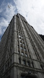 Ground level up view of passenger airplane at high altitude above iconic Chrysler building, New York urban city skyline, United States of America