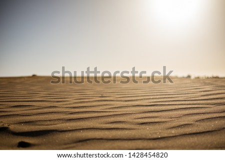 ground level view of desert sand at sunset with sun hitting hard from above giving a sense warm and hot wth nobody