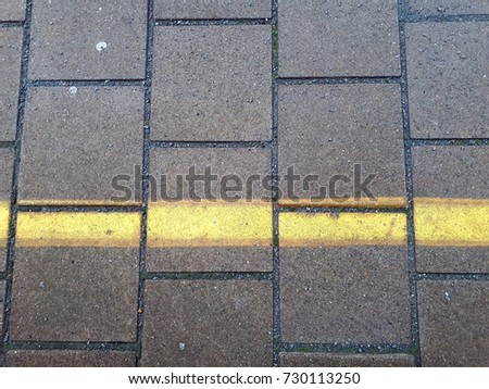 ground of a platform of a train station with square cobbles and yellow warning line #730113250