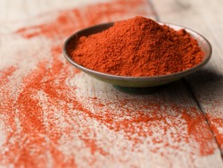 Ground Paprika in a bowl on wooden table