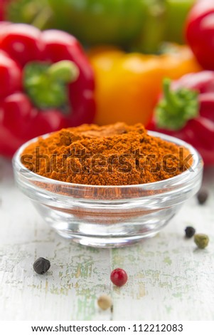 Ground paprika in a glass bowl and fresh pepper