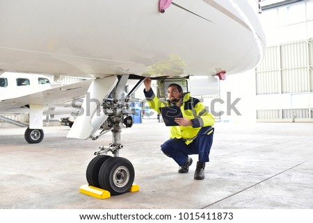 Ground personnel at the airport check the hydraulic system of the landing gear of the aircraft