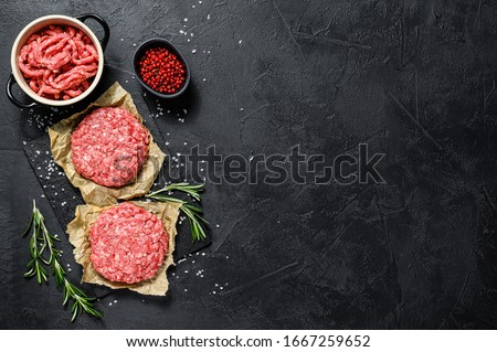 Ground raw meat patties. Meat patties ready to cook. Barbecue party. Farm organic meat. Black background. Top view. Space for text