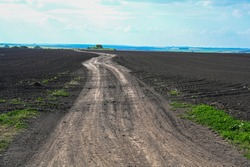 Ground road leaving to the horizon. Agriculture plowed field. Black soil plowed field. Tillage soil prepared for planting crop. Fertile soil in organic agricultural farm. Landscape of farmland.