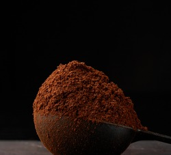 ground roasted coffee arabica in a spoon on a black background, close-up