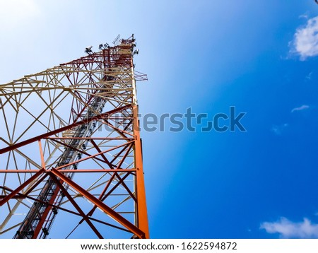 Ground shot of Mobile phone antenna with white cloud and clear blue sky background. Wireless network technology for voice and high speed 4g,5g data usage connection. Base station to boost signal. Сток-фото ©