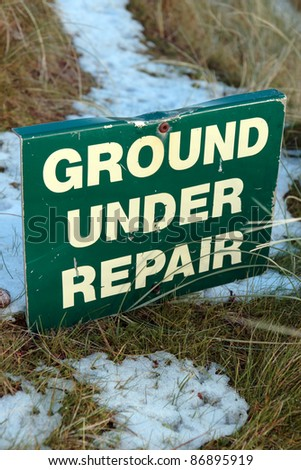 ground under repair sign on a snow covered links golf course in ireland in snowy winter weather