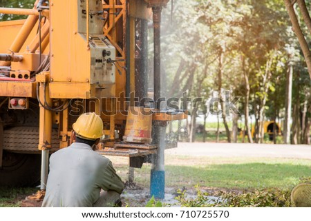Ground water hole drilling machine installed on the old truck in Thailand. Worker keeping an eye on Ground water well drilling. Ground water well drilling.