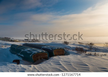 Grounded canoes and small boats on the shore of James Bay in winter, near the northern Cree community of Chisasibi, Quebec.