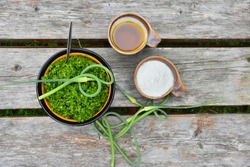 Grounded garlic scapes in a bowl, salt and oil near it on a wooden table. All three ingredients for perfect pesto - healthy beverage for meat, fish or any other meal.