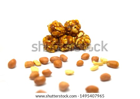 groundnut Chikki ball, an Indian traditional and popular sweet, is made from peanuts and jaggery. and spread groundnut seeds in white background