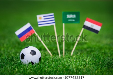 Group A draw in Football match. National Flags of Russia, Saudi Arabia, Egypt, Uruguay. Flags on green grass on football stadium #1077432317