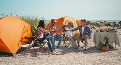 group adult joyful friends relaxing in capm chairs, drinking beer and having fun at beach together. travelers toasting beer and enjoy together in seaside camping. Friendship and celebration concept.