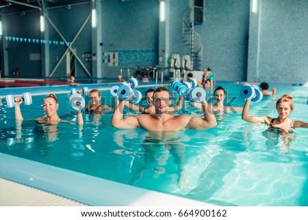 Group aqua aerobics traninig in indoor pool