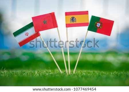 Group B draw in Footbal.National Flags of Portugal, Spain, Morocco, IR Iran. Flags on green grass on football stadium #1077469454