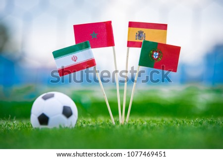 Group B National Flags of Portugal, Spain, Morocco, IR Iran. Flags on green grass on football stadium. #1077469451