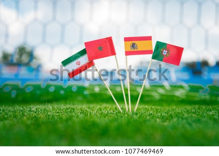 Group B - National Flags of Portugal, Spain, Morocco, IR Iran. Flags on green grass on football stadium. draw in Football match. #1077469469