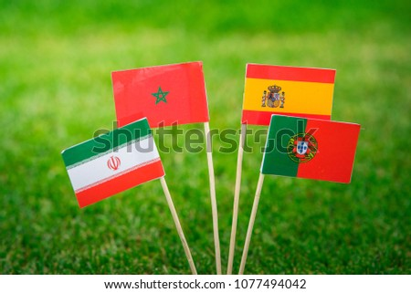 Group B - National Flags of Portugal, Spain, Morocco, IR Iran, Flags on green grass on football stadium #1077494042